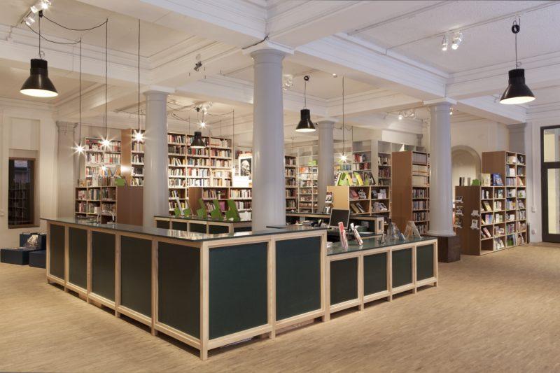 Biblioteksdelen skulle initialt skärmas av med en gallergardin vid annan användning av lokalen, men med tiden insåg beställarna att detta var överflödigt. Till vänster skymtar lite av barnhörnan fram. Foto: Katarina Elven