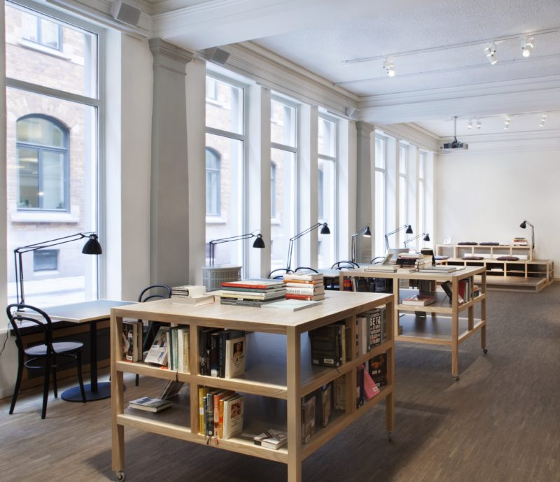 Många språkstudenter passerar biblioteket dagligen och använder det som studieplats. Läshörnan i bakgrunden fungerar som scen vid samtal och uppläsningar. Då kan bokborden rullas undan in i biblioteksdelen och skapa mer plats. Foto: Andrea Johnson