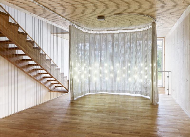 Soft House, radhus i massivträ på IBA Hamburg med rörliga solceller på fasaden och textila väggar inomhus med integrerad belysning. Foto: Michael Moser